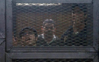 Egyptian activists Ahmed Douma (R) and Ahmed Maher (L), the founder of the April 6 youth movement that led the revolt against ousted president Hosni Mubarak, react as they stand in the accused dock during their trial in the capital Cairo on April 7, 2014. (photo credit: AFP/Hassan Mohamed)