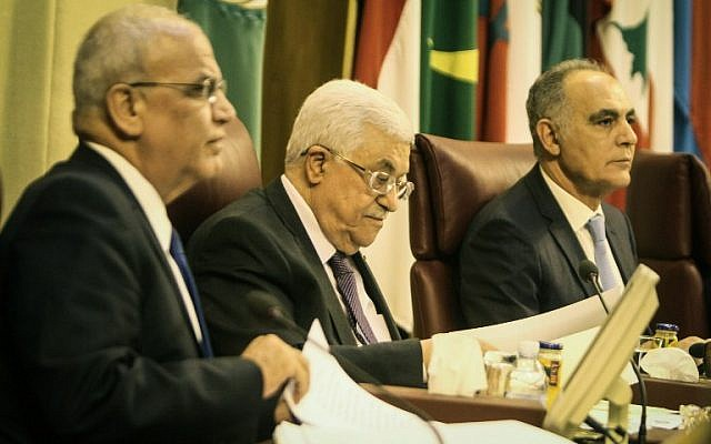Palestinian Authority President Mahmoud Abbas, center, and negotiator Saeb Erekat, left, attend the Arab foreign ministers' meeting at the Arab League headquarters in Cairo, on April 9, 2014. (photo credit:  AFP PHOTO / MOHAMED EL-SHAHED)