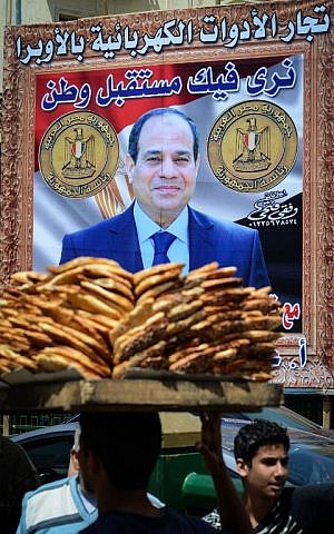 Egyptians walk past a poster bearing a portrait of retired army chief and presidential candidate Abdel Fattah al-Sisi on April 12, 2014 in the capital Cairo. (photo credit: AFP Photo/Mohamed el-Shahed)