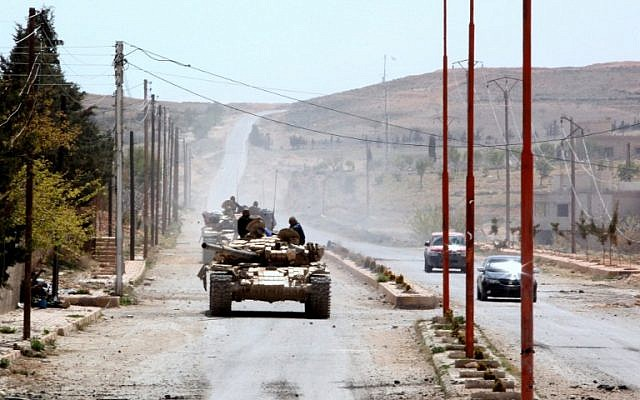 Tanks belonging to government forces drive in al-Sarkhra village, in the Qalamun mountains, northeast of Damascus, after taking control of the village from rebel fighters, on April 14, 2014. (photo credit: AFP/STR)