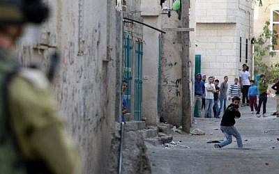 A Palestinian protester uses a slingshot to hurl stones towards Israeli security forces during clashes at the Aida Palestinian refugee camp near Bethlehem on April 14, 2014. (Musa al-Shaer/AFP)
