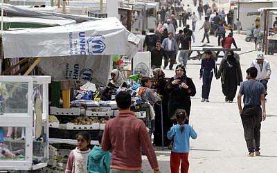 Syrian refugees walks past a makeshift market in the Zaatari refugee camp, on April 15, 2014. (AFP/Khalil Mazraawi)