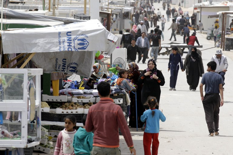 Syrian refugees walks past a makeshift market in the Zaatari refugee camp, on April 15, 2014. (photo credit: AFP/Khalil Mazraawi)