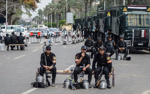 Egyptian policemen sit on benches on a street in the capital Cairo on April 16, 2014.  (photo credit: AFP/Mohamed El-Shahed)