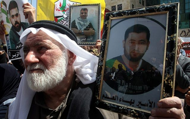 A Palestinian man holds up a portrait of a relative during a demonstration to mark Prisoners Day in Hebron, on April 17, 2014. (photo credit: AFP/Hazem Bader)