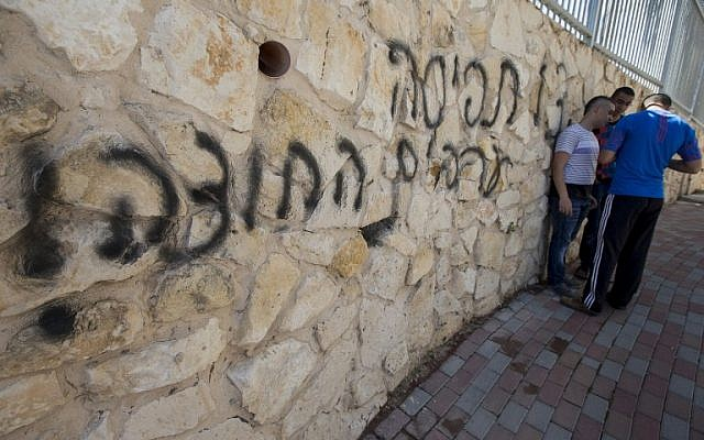 """Arab Israeli men stand next to graffiti reading in Hebrew """"Arabs Out"""" on the wall of a mosque in the northern Israeli city of Umm al-Faham on April 18, 2014. (photo credit: AFP/ JACK GUEZ)"""