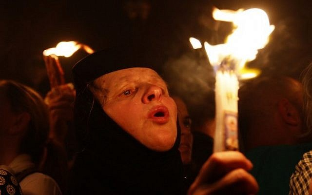 "A Christian Orthodox worshipper holds a candle lit from the ""Holy Fire"" as thousands gather in the Church of the Holy Sepulcher in Jerusalem's old city on April 19, 2014 (Photo credit: Gali Tibbon/AFP)"