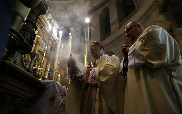 The Latin Patriarch of Jerusalem and Head of the Roman Catholic Church in the Holy Land, Fuad Twal (C), leads an Easter Sunday mass in the Church of Holy Sepulchre in Jerusalem's Old City on April 20, 2014.  (photo credit: AFP PHOTO/GALI TIBBON)