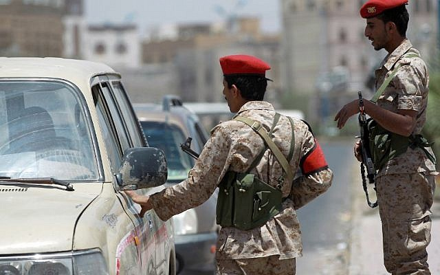 Yemeni soldiers stand guard in the capital Sanaa on April 20, 2014, and check passing vehicles as authorities tightened security measures a day after a US drone killed 15 al-Qaeda suspects (photo credit: AFP/Mohammed Huwais)