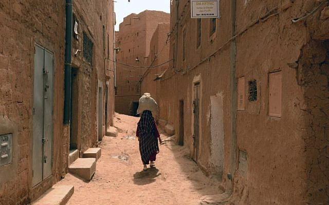 A Moroccan woman carries a sack on her head as she walks along a narrow street in the Jewish Mellah quarter of Tinghir, at the foot of the High Atlas and the heart of Morocco's Berber community on April 21 , 2014 (photo credit: AFP/FADEL SENNA)
