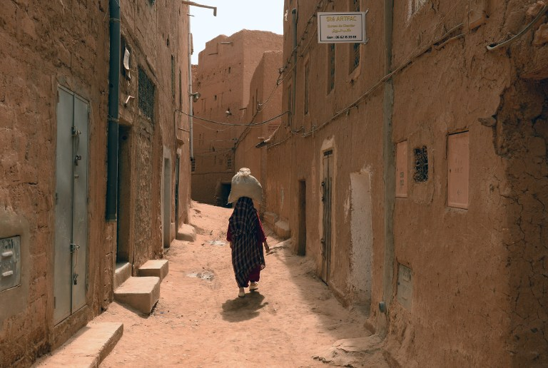 A Moroccan woman carries a sack on her head as she walks along a narrow street in the Jewish Mellah quarter of Tinghir, at the foot of the High Atlas and the heart of Morocco's Berber community on April 21, 2014 (photo credit: AFP/FADEL SENNA)