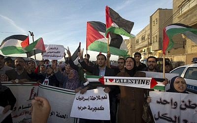 Palestinians wave their national flag as they demonstrate in Gaza City on April 22, 2014. (AFP/Mahmud Hams)