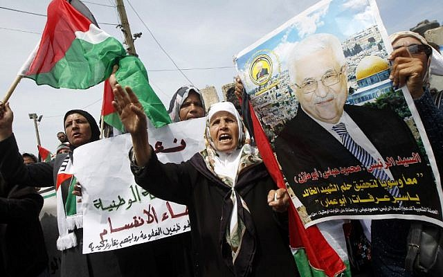 Palestinians shout slogans and hold a portrait of Palestinian president Mahmoud Abbas as they take part in a demonstration in support of a new attempt to reconcile Hamas and the PLO in Gaza City Wednesday. (photo credit: AFP/SAID KHATIB)