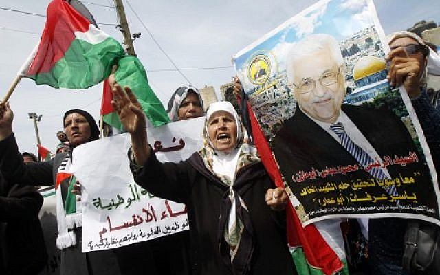 Palestinians shout slogans and hold a portrait of Palestinian leader Mahmoud Abbas (portrait) as they take part in a demonstration in support of a new attempt to reconcile the militant Islamist movement Hamas and its Palestine Liberation Organisation (PLO) April 23, 2014. (photo credit: AFP/SAID KHATIB)