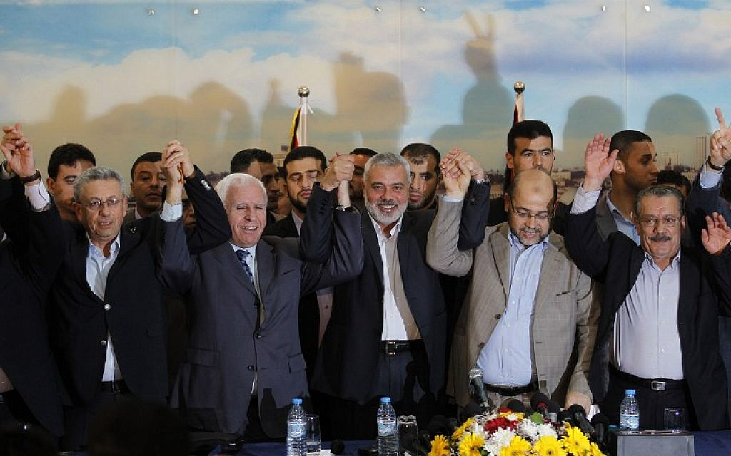 File: From left: Palestinian legislator Mustafa Barghouti, Palestinian Fatah delegation chief Azzam al-Ahmed, Hamas prime minister in the Gaza Strip Ismail Haniyeh, Hamas deputy leader Musa Abu Marzuk, and secretary-general of the Palestinian Arab Front  Jameel Shehadeh, pose for a picture in Gaza on April 23, 2014 after announcing a unity deal. (photo credit:AFP/SAID KHATIB)