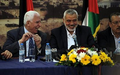 Palestinian Fatah delegation chief Azzam al-Ahmed, left, laughs with Hamas Prime Minister in the Gaza Strip Ismail Haniyeh during a press conference in Gaza on Wednesday (photo credit: AFP/Said Khatib)