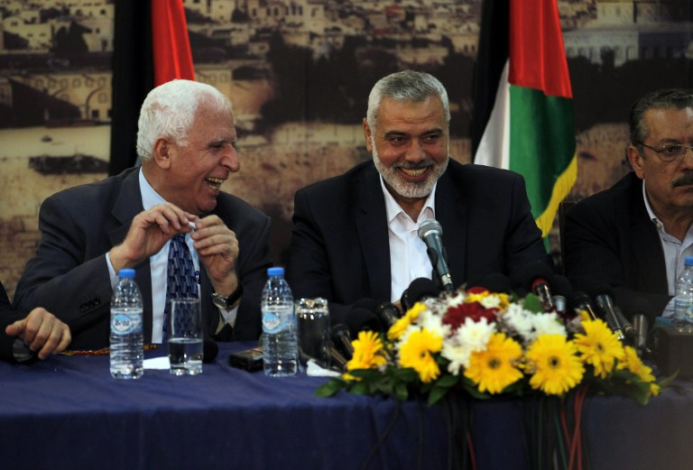 Palestinian delegation chief Azzam Al-Ahmad, left, with then Hamas prime minister in the Gaza Strip Ismail Haniyeh at a press conference in Gaza in April 2014 (AFP/Said Khatib)