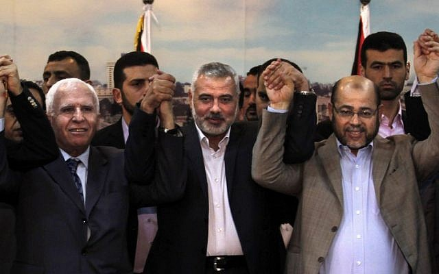 (From L to R) Palestinian Fatah delegation chief Azzam al-Ahmad, Hamas prime minister in the Gaza Strip Ismail Haniyeh and Hamas deputy leader Moussa Abu Marzouk pose for a photo as they celebrate in Gaza City on April 23, 2014, after West Bank and Gaza Strip leaders agreed to form a unity government within five weeks. (photo credit: AFP/Said Khatib)