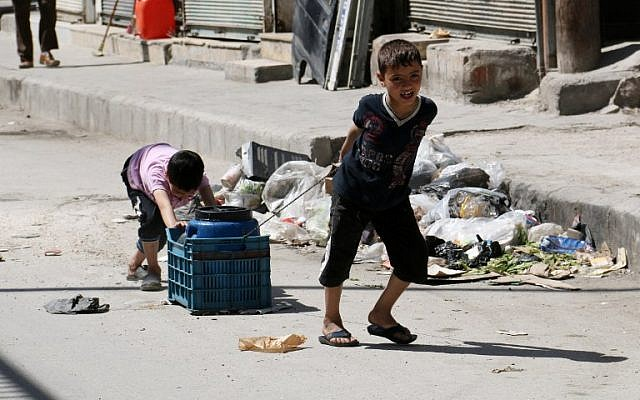 Children carry a cylinder of water in a street of the Syrian city of Aleppo on April 17, 2014. (photo credit: AFP/ALEPPO MEDIA CENTRE/ZEIN AL RIFAI)
