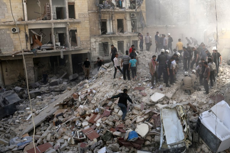 """People inspect the rubble after a building collapsed following a reported bombardment with explosive-packed """"barrel bombs"""" by Syrian government forces in the al-Mowasalat neighborhood of the northern Syrian city of Aleppo, on April 27, 2014. (photo credit: AFP Photo/Aleppo Media Centre/Zein al Rifai)"""