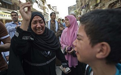 Egyptians react outside the courtroom in Egypt's southern province of Minya on April 28, 2014.  (photo credit:AFP/KHALED DESOUKI)