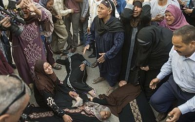 Egyptian women faint outside the courtroom in Egypt's southern province of Minya after an Egyptian court sentenced Muslim Brotherhood leader Mohamed Badie and other alleged Islamists to death, on April 28, 2014. (photo credit: AFP Photo/Khaled Desouki)