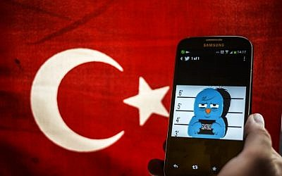This file picture dated on March 26, 2014, shows a picture representing a mugshot of the Twitter bird seen on a smartphone with a Turkish flag in Istanbul. (AFP/Ozan Kose)