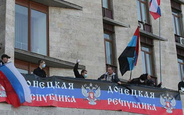 Pro-Russian supporters deploy a Russian flag and the flag of the so-called Donetsk Republica as they storm the regional administration building in the eastern Ukrainian city of Donetsk on April 6, 2014. (photo credit: AFP PHOTO/ Alexander Khudoteply)