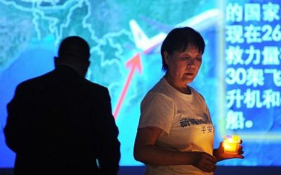 A Chinese relative of passengers on the missing Malaysia Airlines flight MH370 holds a candle as she takes part in a prayer service at the Metro Park Hotel in Beijing on April 8, 2014. photo credit: AFP/WANG ZHAO)