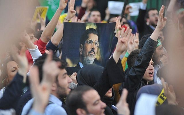 Supporters of the Egyptian Muslim Brotherhood hold a portrait of of deposed president Mohammed Morsi as they take part in a rally to protest against the death penalties for the members of the radical group in Egypt, outside the Egyptian embassy in Ankara on April 9, 2014. A court in Egypt on March 29 sentenced to death two supporters of deposed president Mohamed Morsi convicted of throwing youths off an apartment block roof, judicial sources said. The latest death sentences come despite international outcry at Egypt handing down the death penalty to 529 Islamists. (AFP PHOTO / ADEM ALTAN)