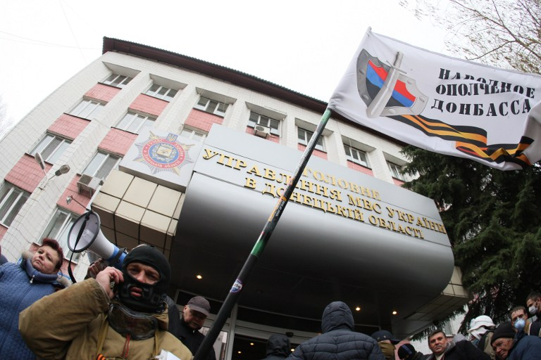 A pro-Russian activists stands outside the regional police headquaters building seized by pro-Russian separatists in the eastern Ukrainian city of Donetsk on April 12, 2014. (photo credit: AFP/ALEXANDER KHUDOTEPLY)