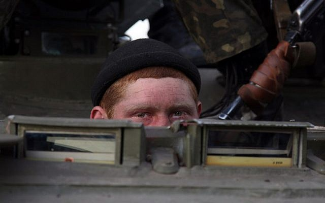 A soldier peeks out as a column of Ukrainian men on Armoured Personnel Carriers were blocked by pro-Russia supporters in the eastern Ukrainian city of Kramatorsk on April 16, 2014.  (AFP/ANATOLIY STEPANO)
