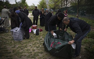 Syrian refugees pack goods on April 21, 2014 in the Edouard Vaillant parc in Saint-Ouen, north of Paris, where they spend most of their days awaiting housing solutions (photo credit: AFP/Joel Saget)