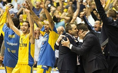 Maccabi Electra Tel Aviv's Head Coach David Blatt, 3rd from right, hugs an unidentified team member as players celebrate after the Euroleague playoffs basketball match, group D, round 4, between Emporio Armani Milan and Maccabi Tel Aviv on April 23, 2014 at the Nokia stadium in Tel Aviv (photo credit: AFP/Jack Guez)