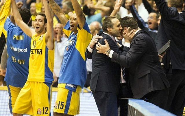Maccabi Tel Aviv's head coach David Blatt, 3rd from right, hugs an unidentified man after the Euroleague playoffs basketball match, group D, round 4, between Emporio Armani Milan and Maccabi Tel Aviv on April 23, 2014 at the Nokia stadium in Tel Aviv (photo credit: AFP/Jack Guez)
