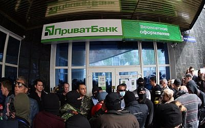 Pro-Russian militants attack a branch of Ukrainian bank Privatbank in the eastern Ukrainian city of Donetsk on Monday, April 28, 2014 (photo credit: AFP/ALEXANDER KHUDOTEPLY)