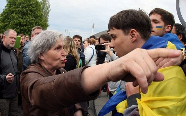 An elderly pro-Russian woman gestures and argues with a young man wearing a Ukrainian flag during a rally for national unity in the eastern Ukrainan city of Donetsk on April 28, 2014. (photo credit: AFP/Alexander Khudoteply)