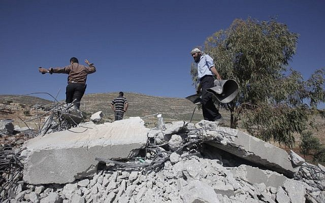 Palestinians inspect the remains of a mosque after it was demolished by Israeli authorities who said it was built without municipal permission on April 29, 2014 (photo credit: AFP/JAAFAR ASHTIYEH)