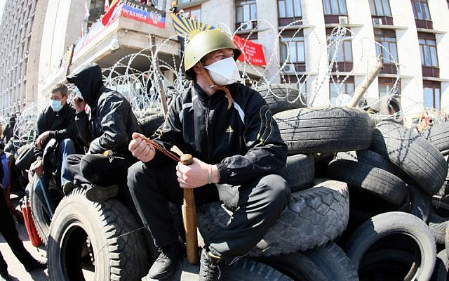 A pro-Russian militant holding a bat guards a barricade in front of the Donetsk regional administration building on April 8, 2014. (photo credit: AFP PHOTO / ALEXANDER KHUDOTEPLY)