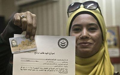 An Egyptian woman poses in Cairo on March 31, 2014  with her ID and a document that she has signed to support the candidacy of former army chief Abdelfatah al-Sissi to run in the presidential elections to be held on May 26-27.  (photo credit: AFP/ KHALED DESOUKI)