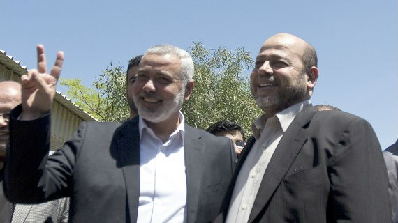 Then-Hamas Prime Minister in the Gaza Strip Ismail Haniyeh (L) flashes the V-sign as he greets the movement's deputy leader, Moussa Abu Marzuk, upon his arrival in Gaza City, on Monday, April 21, 2014 (photo credit: AFP Photo/Mahmud Hams)
