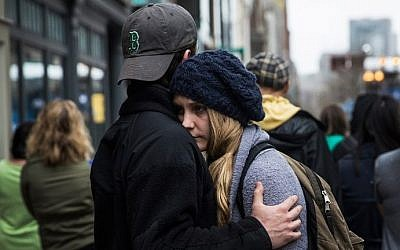 Tom Duggan hugs Sarah Rogo, who said they were both present last year at the marathon, while a billboard television screen broadcasts the ceremony commemorating the one year anniversary of the 2013 Boston Marathon Bombing , on April 15, 2014 in Boston, Massachusetts. (Andrew Burton/AFP)