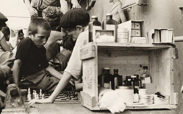 Ruth Gruber. Children playing chess on the refugees' deck of the Henry Gibbins next to an outdoor medical station and pharmacy, 1944. (© Ruth Gruber)