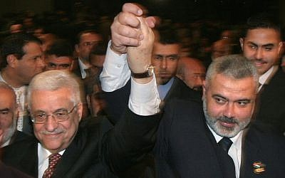 Palestinian Authority President Mahmoud Abbas, left, and then Hamas prime minister Ismail Haniyeh, right, raise their linked arms as they move through the crowd at a special session of parliament in Gaza City, March 17, 2007. (AP/Hatem Moussa/File)