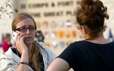 Krystina Cassidy, left, and Dianna Simpson attempt to make contact with their husbands who are stationed inside Fort Hood while standing outside of the Bernie Beck Gate on Wednesday, April 2, 2014, in Fort Hood, Texas. (photo credit: AP/Tamir Kalifa)