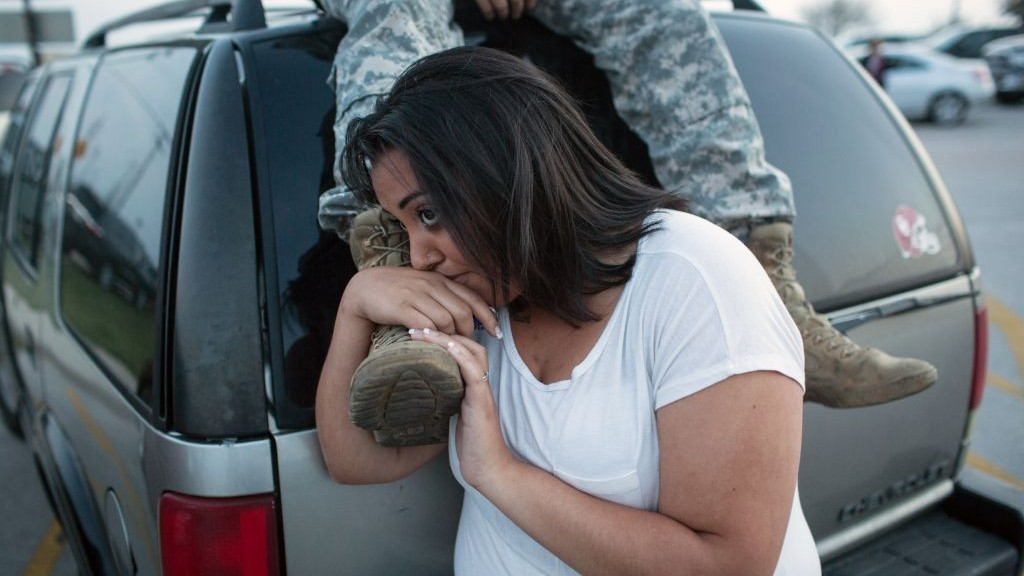 Lucy Hamlin and her husband, Spc. Timothy Hamlin, wait for permission to re-enter the Fort Hood military base, where they live, following a shooting on the base, Wednesday, April 2, 2014, in Fort Hood, Texas. (photo credit: AP/Tamir Kalifa)