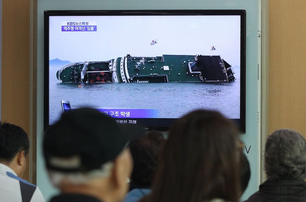 People watch a TV news program showing a sinking passenger ship, at Seoul Railway Station in Seoul, South Korea, Wednesday, April 16, 2014 (photo credit: AP/Ahn Young-joon)