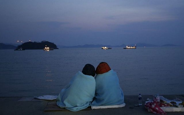 Relatives of passengers aboard the sunken ferry Sewol sit near the sea at a port in Jindo, south of Seoul, South Korea, Sunday, April 20, 2014. (AP Photo/Lee Jin-man)
