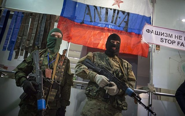 Masked pro-Russian gunmen guard an entrance to the Ukrainian regional office of the Security Service, with a Russian National flag in the background, in Luhansk, Ukraine, Monday, April 21, 2014 (photo credit: AP/Alexander Zemlianichenko)