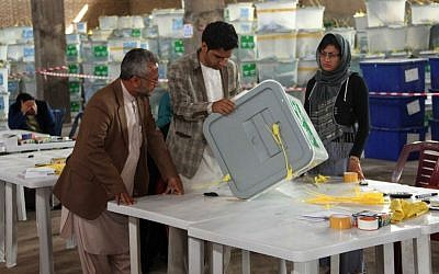 Afghan ballot counters read instructions on how to count and register votes in Herat Province, west of Kabul, Afghanistan, Sunday, April 20, 2014. (AP Photo/Hoshang Hashimi)